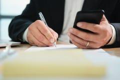 Ręki Pisze Z piórem I Trzyma telefon Biznesowy mężczyzna zdjęcie royalty free