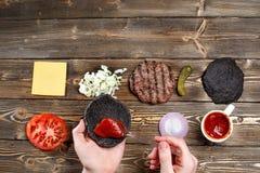 Ręki podnosić hamburger, rozprzestrzeniają ketchup na babeczce Ciemny restauracyjny menu, hamburgerów składniki i kopii przestrze Zdjęcia Stock