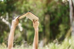 Ręki podnosi książkę do czytający obraz royalty free