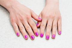 Ręki pokazują pięknego manicure na stole Przybija purpury, menchie zdjęcia royalty free