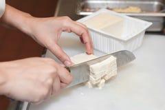Ręki pokazywać ciący tofu blok w kawałki z nożem obraz stock