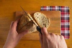 Ręki pokrajać bochenek niskokaloryczny chleb z flaxseeds z rżniętym plasterkiem na w kratkę pielusze i W naturalnym świetle zdjęcia royalty free