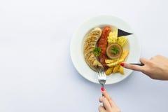 Ręki pokrajać piec na grillu kiełbasy z kumberlandu ketchupem na talerzu wierzchołek Zdjęcie Royalty Free