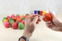 Ręki potomstwo relaksujący mężczyzna maluje kolorowych jajka na marmuru wierzchołku z copyspace tłem przygotowywa Easter dzień Fotografia Royalty Free