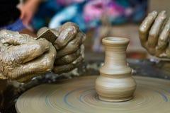 Ręki pracuje na ceramicznym kole, zamykają up Zdjęcie Stock