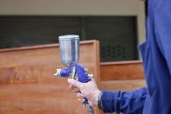 Ręki przemysłowego pracownika mienia kiści farby pistolet w fabryce Obrazy Stock