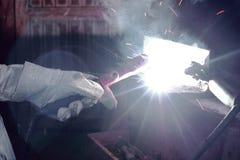 Ręki przemysłowy pracownik z pochodnia metalu spawalniczą stalą z iskrze w warsztacie fotografia royalty free