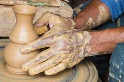 Ręki robić glinianemu garnkowi na ceramicznym kole, wybrana ostrość, zakończenie zdjęcia stock