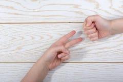 Ręki robi skale, papier, nożyce gestykulują na drewnianym tle obraz stock