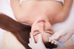 Ręki robi zastrzykowi w twarzy cosmetologist, wargi Młoda kobieta dostaje pięknu twarzowych zastrzyki w salonie Twarzy starzenie  Obrazy Stock