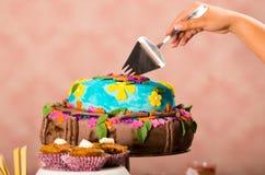 Ręki rozcięcie w wyśmienicie kolorowego tort używać metal kuchni narzędzie, różowy tapetowy tło, ciasta pojęcie Zdjęcia Stock