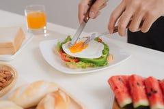 Ręki słuzyć z chlebem mężczyzna cięcie jajka na papierze, ziele, sa Obrazy Stock