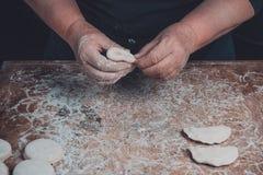 Ręki stara babcia pleśnieją vareniks na ciemnym tle obrazy stock