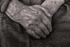 Ręki stara kobieta składali w jej podołku, czarny i biały Zdjęcie Stock