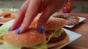 Ręki stawiają świeżej liść sałaty na hamburgerze zbiory wideo