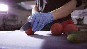 Ręki szef kuchni pokrajać w górę pomidoru z nożem na tnącej desce w rękawiczkach zbiory
