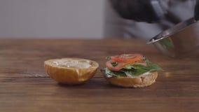 Ręki szef kuchni w czarnych kuchennych rękawiczkach robi hamburgerowi w górę Kucbarscy kładzenie pomidoru plasterki na basilu opu zbiory