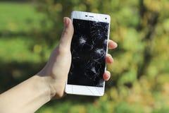 Ręki trzyma łamanego mądrze telefon fotografia stock