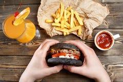 Ręki trzyma świeżych wyśmienicie hamburgery z francuskimi dłoniakami, kumberland, świeży sok pomarańczowy i alkoholiczka koktajl  zdjęcie stock