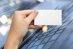 Ręki trzyma białą biznesową wizyty id kartę, prezent, bilet, przepustka, teraźniejszy seansu zakończenie up na zamazanym błękitny Zdjęcie Royalty Free