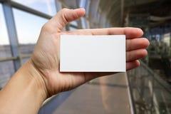 Ręki trzyma białą biznesową wizyty id kartę, prezent, bilet, przepustka, teraźniejszy seansu zakończenie up na zamazanym błękitny Obrazy Stock