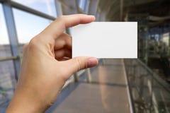 Ręki trzyma białą biznesową wizyty id kartę, prezent, bilet, przepustka, teraźniejszy seansu zakończenie up na zamazanym błękitny Fotografia Stock