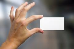 Ręki trzyma białą biznesową wizyty id kartę, prezent, bilet, przepustka, teraźniejszy seansu zakończenie up na zamazanym błękitny Zdjęcie Stock
