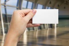 Ręki trzyma białą biznesową wizyty id kartę, prezent, bilet, przepustka, teraźniejszy seansu zakończenie up na zamazanym błękitny Obrazy Royalty Free