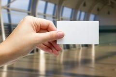 Ręki trzyma białą biznesową wizyty id kartę, prezent, bilet, przepustka, teraźniejszy seansu zakończenie up na zamazanym błękitny Obraz Stock