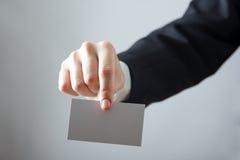 Ręki trzyma białą biznesową wizyty kartę, prezent, bilet, przepustka, teraźniejszość zamknięta up na zamazanym błękitnym tle kosm Zdjęcie Stock