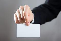 Ręki trzyma białą biznesową wizyty kartę, prezent, bilet, przepustka, teraźniejszość zamknięta up na zamazanym błękitnym tle kosm Obrazy Stock