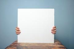 Ręki trzyma białą deskę przy biurkiem fotografia royalty free