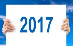 Ręki trzyma białą deskę z 2017 niebieskiego nieba tłem Fotografia Stock
