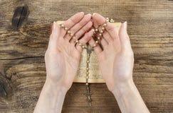 Ręki trzyma biblię i ono modli się z różanem Obraz Stock