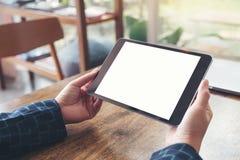 Ręki trzyma czarnego pastylka komputer osobistego z pustym białym desktop ekranem, laptopem na drewnianym stole w kawiarni i Fotografia Royalty Free