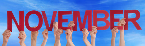 Ręki Trzyma Czerwonego Prostego słowo Listopadu niebieskie niebo Obraz Stock