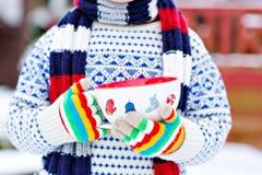 Ręki trzyma dużą filiżankę z płatkami śniegu i gorącym ch małe dziecko Zdjęcie Stock