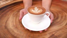 Ręki trzyma filiżankę gorąca latte cappuccino kawa na drewnianym stole Obraz Royalty Free