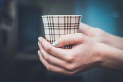 Ręki trzyma gorącą filiżankę kawy lub herbaty w ranku zdjęcie royalty free