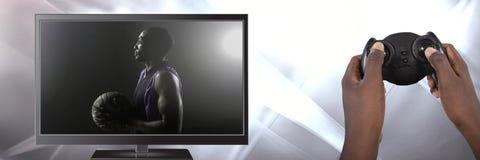 Ręki trzyma hazardu kontrolera z koszykówką na telewizi Obraz Royalty Free