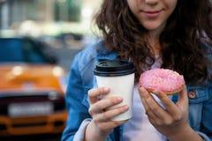Ręki trzyma kawę na tle ruchliwie metropolia i pączek zdjęcia royalty free