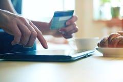 Ręki trzyma kredytową kartę i pastylkę Zdjęcia Stock