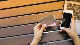 Ręki trzyma kredytową kartę i używa laptop, mądrze telefon Fotografia Royalty Free