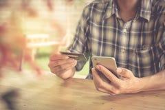 Ręki trzyma kredytową kartę i używa mądrze telefon dof ręce karty ogniska płytki zakupy online bardzo Obraz Royalty Free