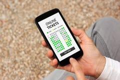Ręki trzyma mądrze telefon z onlinym bileta pojęciem na ekranie Obraz Stock