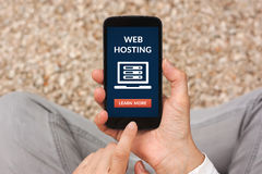 Ręki trzyma mądrze telefon z web hosting pojęciem na ekranie Zdjęcia Stock