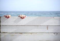 Ręki trzyma na drewnianej ścianie przeciw morzu Zdjęcie Stock