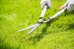 Ręki trzyma ogrodnictwo nożyce na zielonej trawie Obrazy Stock