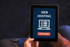 Ręki trzyma pastylkę z web hosting pojęciem na ekranie Fotografia Stock