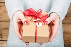 Ręki trzyma prezent w Kraft pudełku na drewnianym tle Obrazy Stock